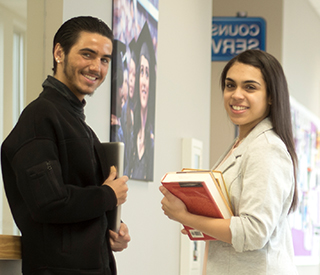 Photo of 2 students holding books in hallways with 3 students in the background mobile image