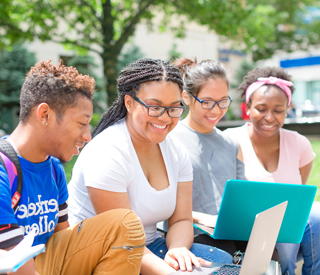 Photo of 是rkeley College students on a laptop outdoors. mobile image